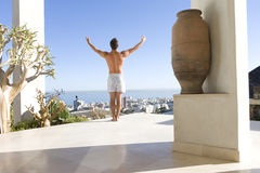Young man standing on balcony, arms outstretched, rear view Royalty Free Stock Image