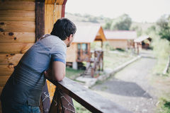 Young man standing on a balcony Royalty Free Stock Photography