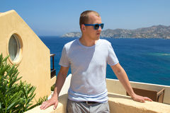 Young man standing on balcony with sea view. Young man standing on balcony with beautiful sea view royalty free stock image