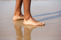 Young man standing with bare feet on beach. Close up portrait of young man standing with bare feet on beach Stock Images