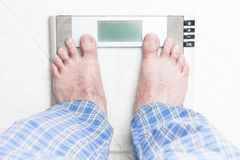 Young man standing on bathroom scale Royalty Free Stock Image