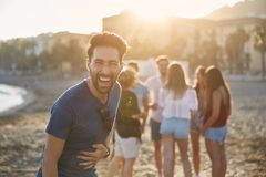 Young man standing on beach with friends laughing stock image