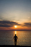 Young man standing at the beach in front of amazing sea view at sunset or sunrise and thinking about his future. Rear royalty free stock photo