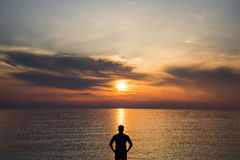 Young man standing at the beach in front of amazing sea view at sunset or sunrise and thinking about his future. Rear view royalty free stock image
