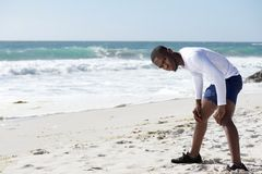 Young man standing on beach with hands on knees. Young african american man standing on beach with hands on knees royalty free stock photo