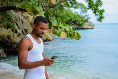 Young man standing at beach with phone in hand staring at phone screen royalty free stock images