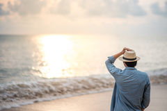 Young man standing on the beach and see beautiful sunset. Young man with jean shirt and hat standing on the beach and see beautiful sunset, vacation time and Stock Images