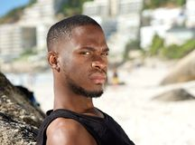 Young man standing at the beach with serious expression Royalty Free Stock Images