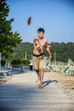 Young man standing at the beach throwing loafer Royalty Free Stock Images