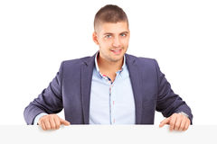 Young man standing behind a blank panel Royalty Free Stock Image