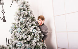 Young man standing behind a Christmas tree Royalty Free Stock Image