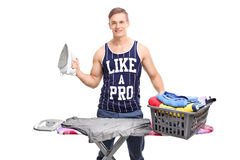 Young man standing behind an ironing board Royalty Free Stock Images