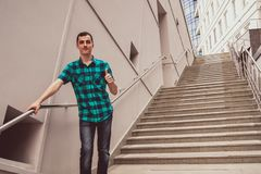 The young man is standing on the big stairs royalty free stock photography