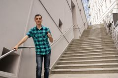 The young man is standing on the big stairs stock photography