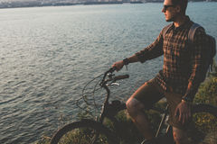 Young Man Standing With Bike On Coast And Enjoying View of Nature Sunset Vacation Traveling Relaxation Resting Concept. A young man cyclist with a backpack in Royalty Free Stock Photography