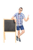 Young man standing by a blackboard Royalty Free Stock Photography