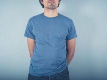Young man standing by blue wall stock image