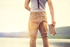 Young Man standing with book outdoor with scandinavian lake on background Royalty Free Stock Photos