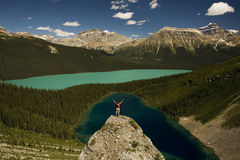 Young man standing on boulder above lakes. Young man standing on boulder and looking toward turquoise alpine lakes of Canadian Rocky Mountains Royalty Free Stock Image