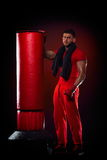 Young man standing by boxing bag Royalty Free Stock Photos