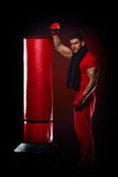 Young man standing by boxing bag Stock Photos