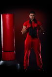 Young man standing by boxing bag Royalty Free Stock Photo