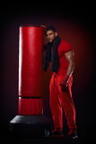 Young man standing by boxing bag in studio Stock Photos