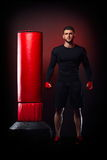 Young man standing by  boxing bag in studio Stock Image
