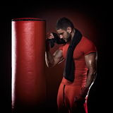Young man standing by boxing bag in studio Royalty Free Stock Photos