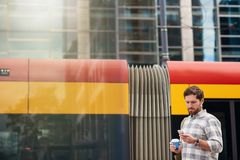 Young man standing at a bus stop reading text messages Stock Images