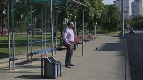 Young man is standing at a bus stop waiting for the bus. Businessman in trousers and shirt is nervous and looks at his watch standing at a station of public stock footage