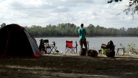 Young man standing in camp on background tourist tent and chairs on bank river. On summer day back view stock video