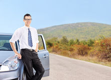 Young man standing by a car on an open road Royalty Free Stock Image