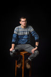 Young man standing on a chair and holding old camera on dark bac Royalty Free Stock Images