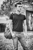 Young man standing in city environment, with backsack Royalty Free Stock Photography