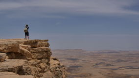 Young man standing on cliff edge and taking panoramic photo of the desert on his phone stock video