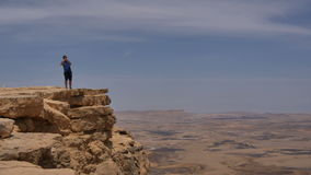 Young man standing on cliff edge and taking pictures of the desert on his phone stock video