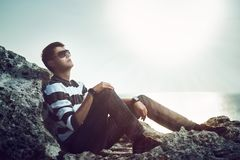 Young man standing on a cliff at sunset Royalty Free Stock Photos