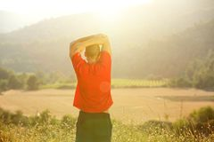 Young man standing in countryside stretching exercise Stock Photos