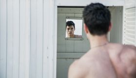Young Man Standing in Doorway of Rustic Beach Hut Royalty Free Stock Images