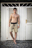 Young Man Standing in Doorway of Rustic Beach Hut Royalty Free Stock Photos