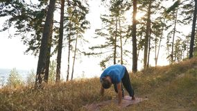 Young man standing in the Downward Facing Dog position in the wood under river