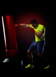 Young man standing exercising with  boxing bag Stock Images