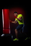 Young man standing exercising with  boxing bag Royalty Free Stock Photography