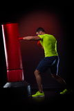 Young man standing exercising with  boxing bag Stock Photo
