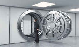 Young man standing in front of a big unlocked round metal safe i Royalty Free Stock Photos