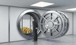 Young man standing in front of a big unlocked round metal safe i Stock Images