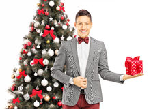 Young man standing in front of a Christmas tree with present Royalty Free Stock Photo