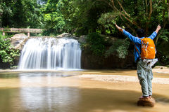 Young man standing in front of waterfall with hand outstretched Royalty Free Stock Photo