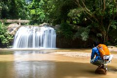 Young man standing in front of waterfall with looking at waterfa. Ll and travel backpack in Thailand Stock Photography